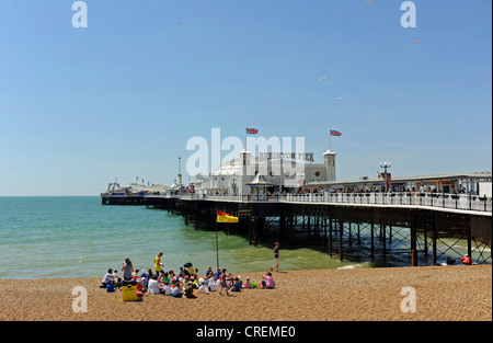Group of young schoolchildren wearing sun hats on beach by Brighton Pier Sussex UK - Stock Photo