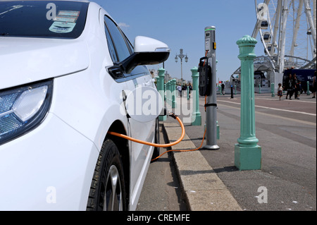 Car plugged into electric power charging point Brighton seafront UK - Stock Photo