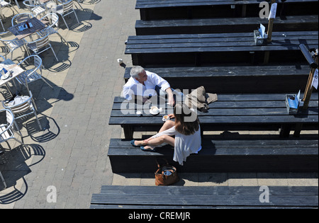 Couple photographed from above enjoying a cup of coffee in sunshine Brighton seafront cafe bar UK - Stock Photo