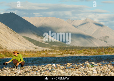 Young woman washing dishes in a river, camping, gravel bar, Mackenzie Mountains behind, Wind River, Peel Watershed - Stock Photo