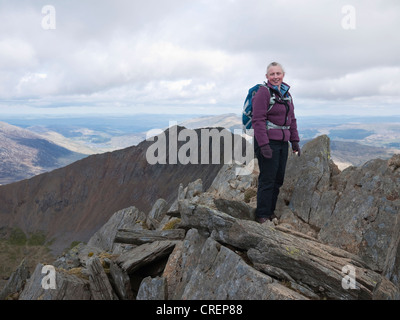 A female hill walker on Crib y Ddysgl / Garnedd Ugain, with Crib Goch in the background - part of the classic Snowdon - Stock Photo