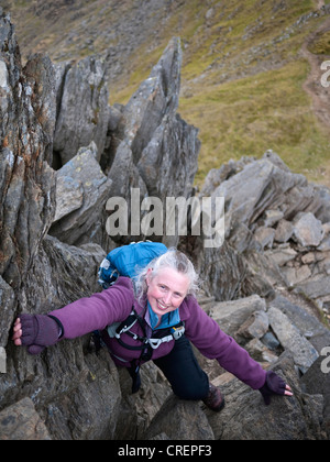 A female hill walker scrambling on Crib y Ddysgl - part of the classic Snowdon Horseshoe route - Stock Photo