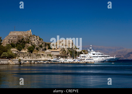 Luxury yachts in front of the Old Fortress, Corfu town, also known as Kerkira, Corfu Island, Ionian Islands, Greece - Stock Photo