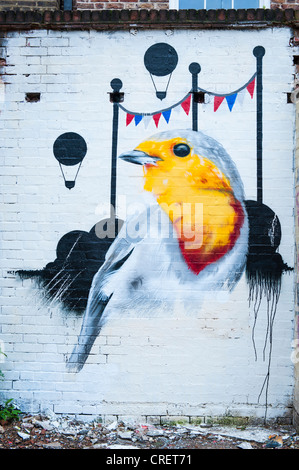 London East End Brick Lane area graffiti street art mural yellow & white finch like bird black balloons pennants - Stock Photo
