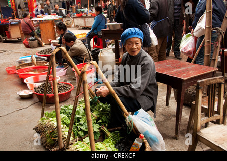 A mature woman selling vegetables at Rongjiang market, Southern China - Stock Photo