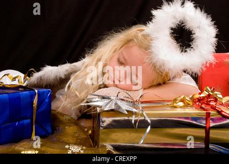 little girl as Christ Child sleeping on presents - Stock Photo