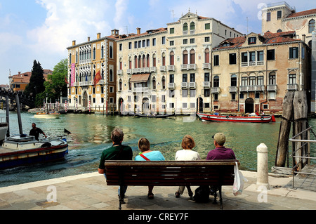 Grand Canal Venice with four seated tourists in foreground - Stock Photo