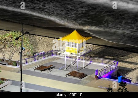 LifeSaver watch tower at deserted beach at night illuminated by street lighting