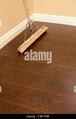 push broom on a newly installed laminate floor and new baseboards stock photo