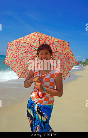 young girl walking with a umbrella on a beach of Ko Samui, Thailand - Stock Photo