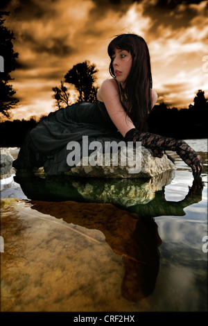 young woman lying on a stone at the water - Stock Photo
