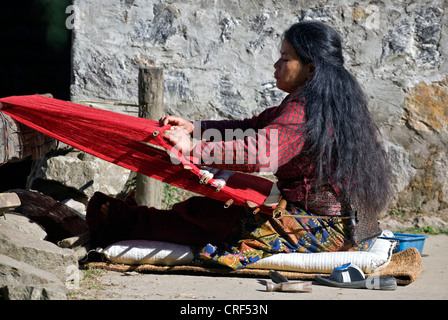 A tribal woman uses a BACKSTRAP LOOM to make red cloth in GYASUMDO VILLAGE near Manang on the ANNAPURNA CIRCUIT, - Stock Photo