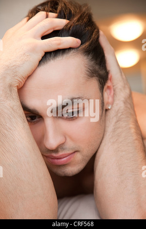 Close-up of a worried young man lying on bed - Stock Photo