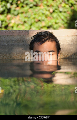 Portrait of serious young man's face on lake water surface - Stock Photo