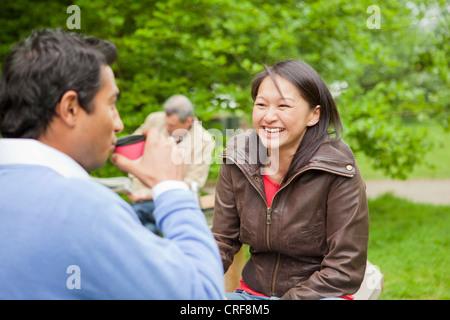 Couple having coffee in park - Stock Photo