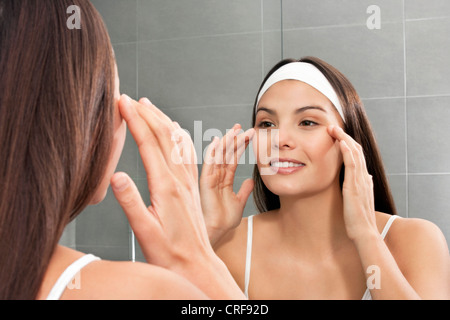 Woman examining her face in mirror - Stock Photo