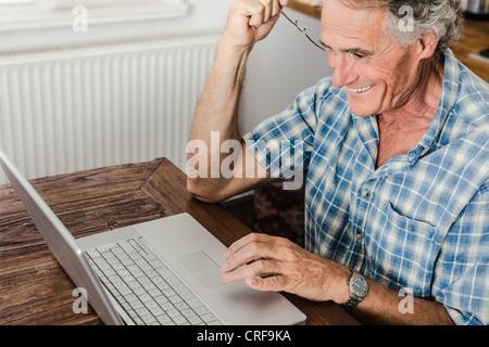 Older man using laptop in kitchen - Stock Photo