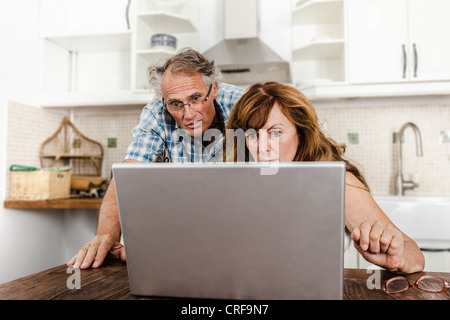 Older couple using laptop in kitchen - Stock Photo