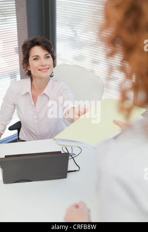Businesswoman turning in folder to boss - Stock Photo