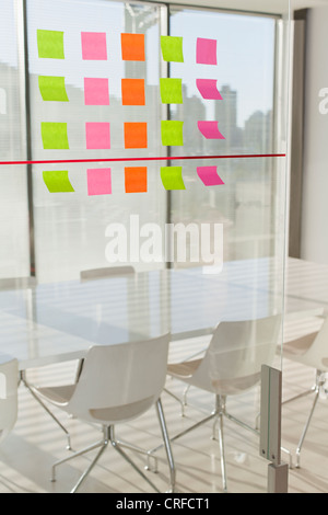 Colorful sticky notes on office window - Stock Photo