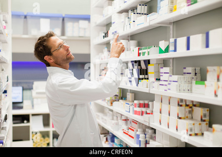 Pharmacist browsing medicines on shelf - Stock Photo