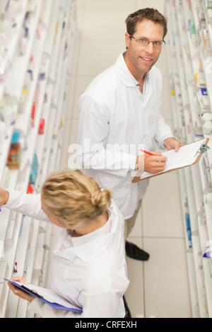 Pharmacists browsing medicines on shelf - Stock Photo