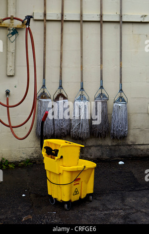 5 Mops hanging on a wall behind a mop bucket - Stock Photo