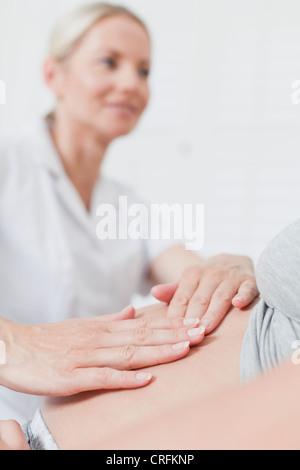 Doctor examining pregnant womans belly - Stock Photo