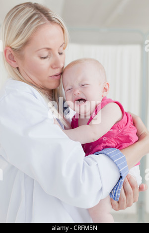 Doctor hugging crying baby - Stock Photo
