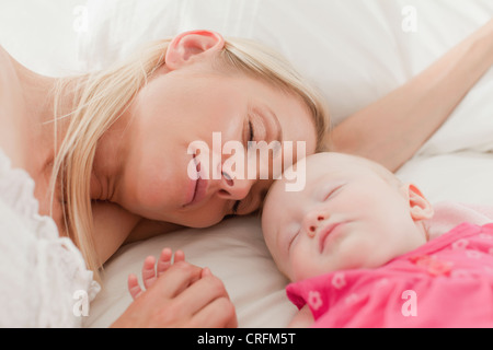 Mother and baby sleeping on bed - Stock Photo