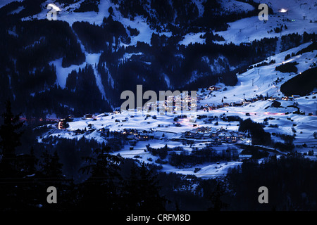 Lit village in snowy landscape at night - Stock Photo