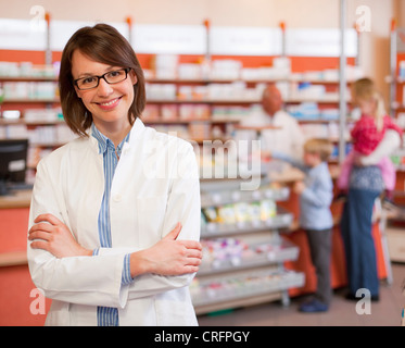 Smiling pharmacist standing in store - Stock Photo