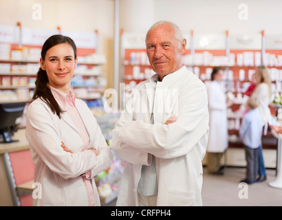 Smiling pharmacists standing in store - Stock Photo