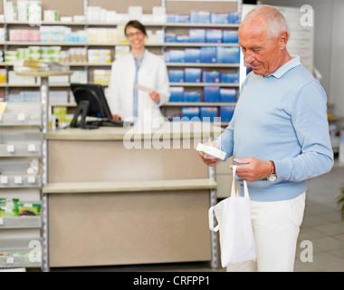 Man picking up prescription at pharmacy - Stock Photo