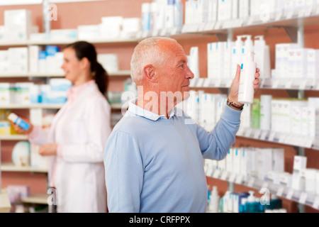 Customer browsing on drugstore shelves - Stock Photo