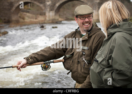 Couple fishing for salmon in river - Stock Photo