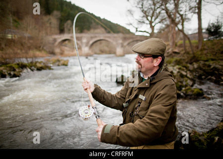 Man fishing for salmon in river - Stock Photo