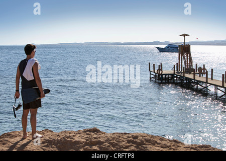 Snorkeler carrying fins on sandy beach - Stock Photo