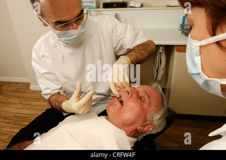 Watched by his assistant, a dentist injects a local pain killing anaesthetic into a patient's gum to numb the surrounding - Stock Photo