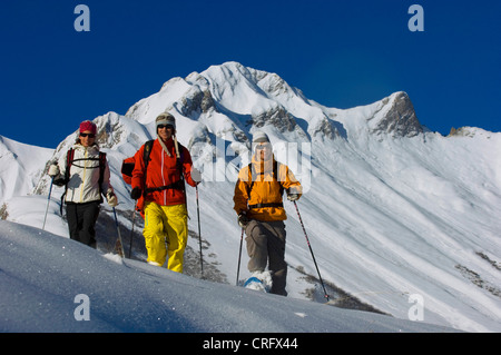 three persons on snow shoes, walking in deep powder snow in the North of Alps near Les Menuires ski resort, France, - Stock Photo