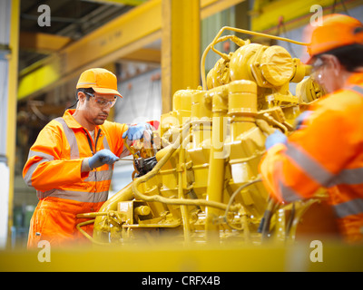 Apprentice engineers at work in factory - Stock Photo