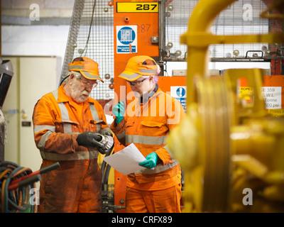Engineer teaching apprentice in factory - Stock Photo