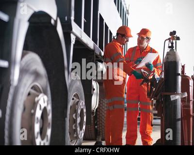 Engineer teaching apprentice outdoors - Stock Photo
