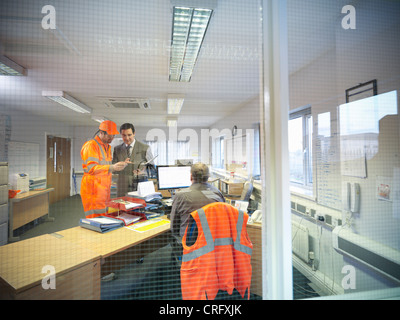 Apprentice engineer with businessman - Stock Photo
