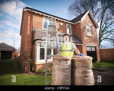 Contractor with rolls of insulation - Stock Photo