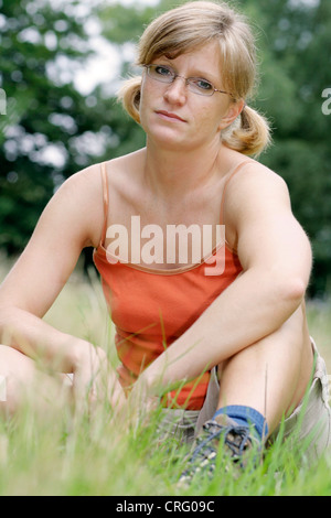 reflective young blond, sportive woman wearing glasses and casual wear, sitting in a meadow - Stock Photo