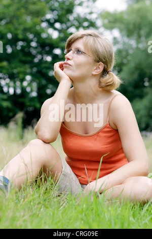 young blond, sportive woman wearing glasses and casual wear, sitting in a meadow - Stock Photo