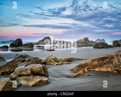 Sunrise and full moonset with reflection at Harris Beach State Park, Oregon - Stock Photo