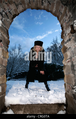 blond woman wearing black fur coat and fur cap standing in snow and looking through an archway - Stock Photo