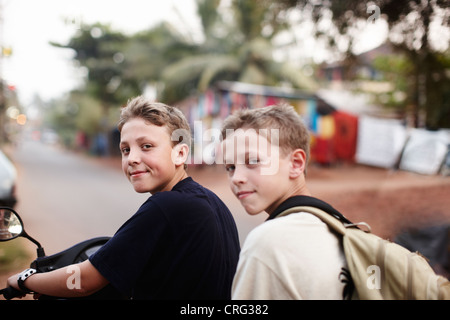 Teenage boys riding scooter on dirt road - Stock Photo